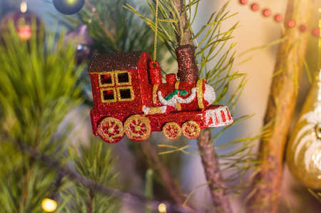 New Year and Christmas toy in a shape of colorful train hanging on a Christmas tree surrounded by other toys ans lights.