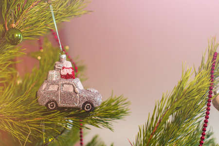 New Year and Christmas toy in a shape of silver car with gifts on the roof hanging on a Christmas tree surrounded by other toys ans lights.