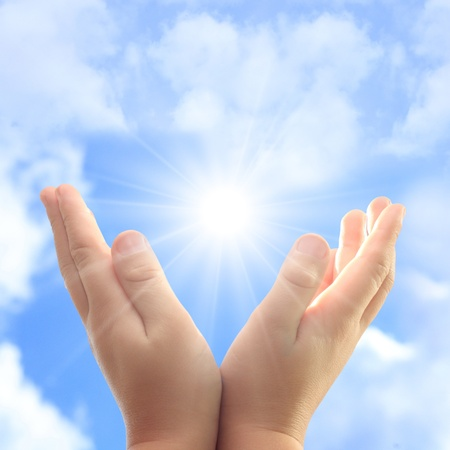 Child hands against blue sky and sun