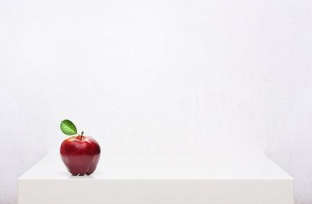 Red apple on the white shelf photo