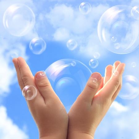 pompas de jabon: Las burbujas de jab�n en las manos del ni�o contra el cielo azul. Foto de archivo