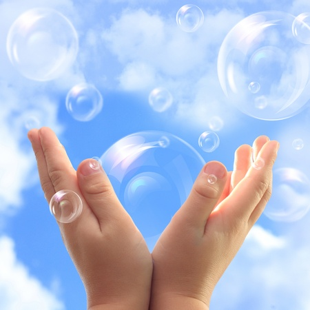 Soap bubbles in child hands against blue sky. photo