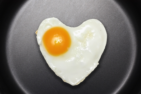 Fried egg like heart on frying pan  photo