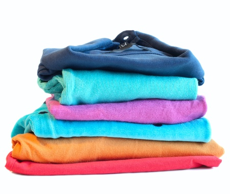 Pile of coloured clothes from the laundry - isolated on white photo
