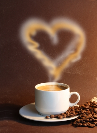 Cup of coffe with steam like heart on brown background photo
