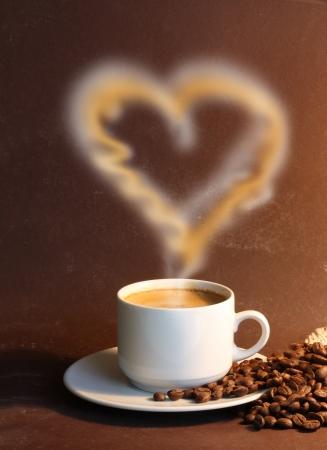 capuchinos: Taza de café con vapor de agua como el corazón sobre fondo marrón Foto de archivo
