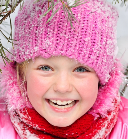 Little happy girl in winter pink hat in snow  photo