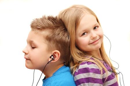 la escucha activa: Chico y chica escuchando música, aislados en fondo blanco Foto de archivo