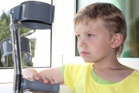 crutches: Seven years old boy with crutches sadly looks out of the window Stock Photo