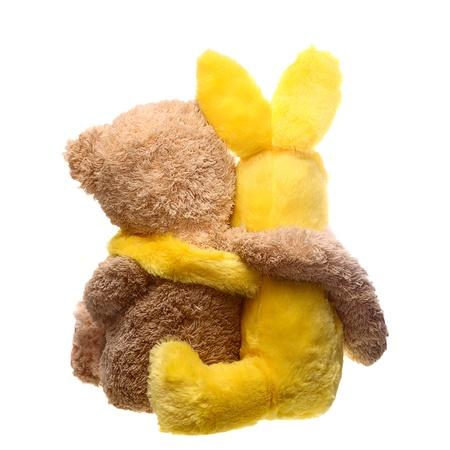 Back view of two toys hugging each other over white Stock Photo