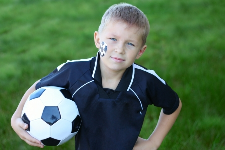A young boy with painted face and soccer ball  photo