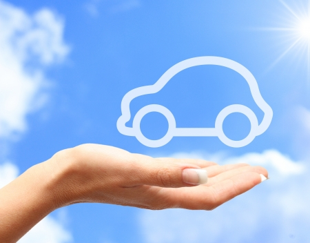 safe driving: Hand with car against blue sky background