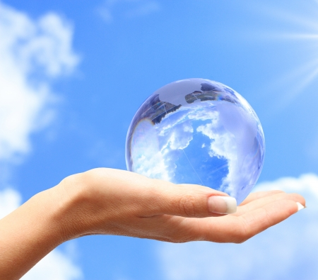 global warming: Globe in human hand against blue sky  Environmental protection concept