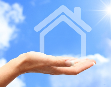 Abstract house in women hand against blue sky photo