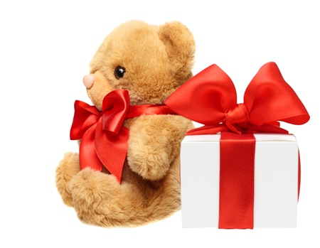 lovable: Classic teddy bear with red bow and present box isolated on white background Stock Photo