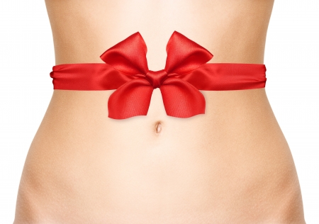 Woman belly with red bow isolated on white background