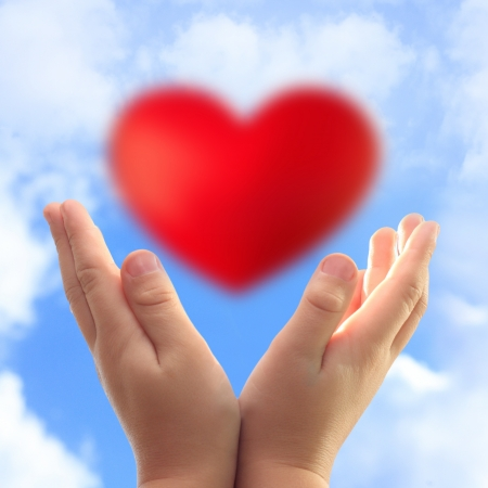 Hands holding heart against blue sky  Stock Photo - 19660478