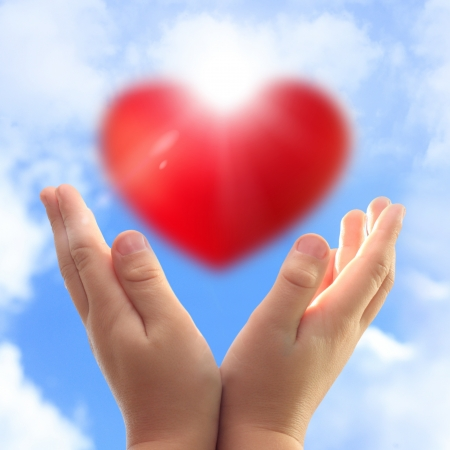 corazon en la mano: Manos que sostienen el coraz�n contra el cielo azul