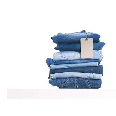 Pile of blue jeans with tag label on white shelf in shop. Stock Photo - 20076119