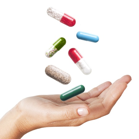 painkillers: Woman hand with falling pills isolated on white background  Stock Photo