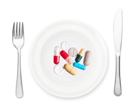 take medicine: Plate with pills, fork and knife isolated on white background.