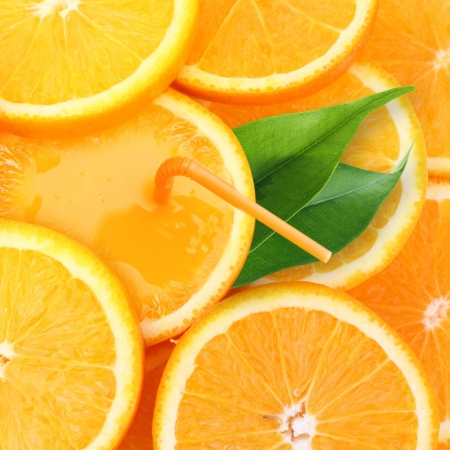 Stack of orange fruit slices with juce background. photo