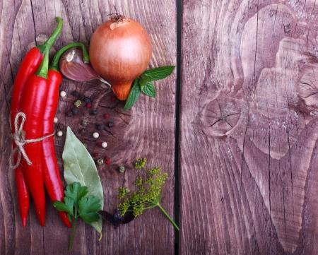 chiles picantes: Pimienta de chiles rojos y especias sobre fondo de madera.