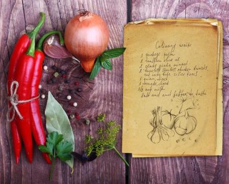 cocina vieja: Especias y viejo libro de recetas en el fondo de madera.