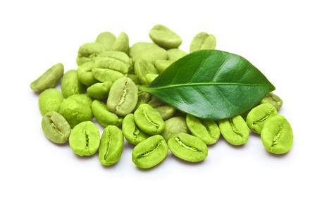Grüne Kaffeebohnen mit Blatt auf weißem Hintergrund.
