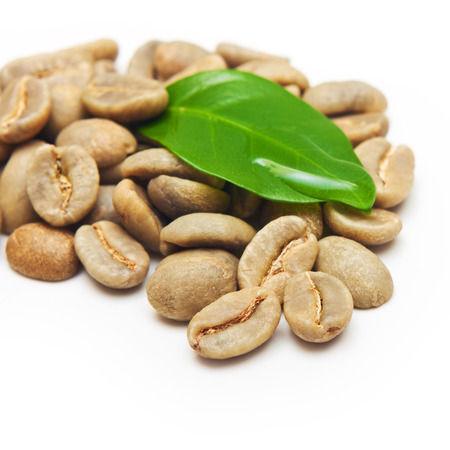 Green coffee beans with leaf on white background. Stock Photo