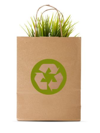 reciclaje papel: De compras de papel bolso del eco con la hierba verde aislado sobre fondo blanco. Foto de archivo