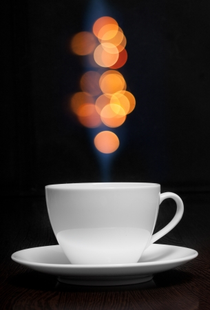 Coffee cup with smoke and abstract bokeh against black wall. photo