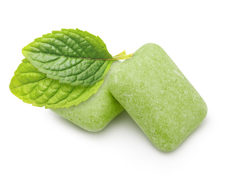 chewing gum: Two chewing gum with mint leaves on white background. Stock Photo