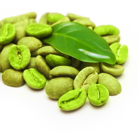 green' white: Green coffee beans with leaf on white background. Stock Photo
