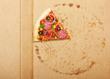Salami pizza slice over box. Stock Photo