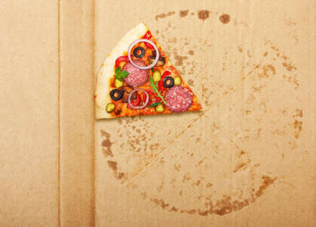 on top of: Salami pizza slice over box. Stock Photo