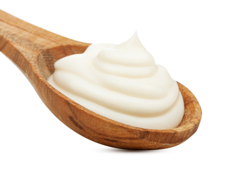 Cream in wooden spoon isolated on white background.