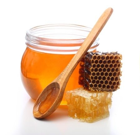 Glass bowl with honey, spoon and slice honey comb isolated on white background