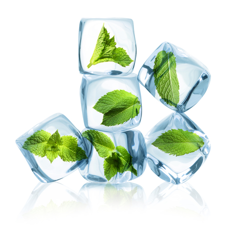 Ice cubes with green mint leaves isolated on white background.