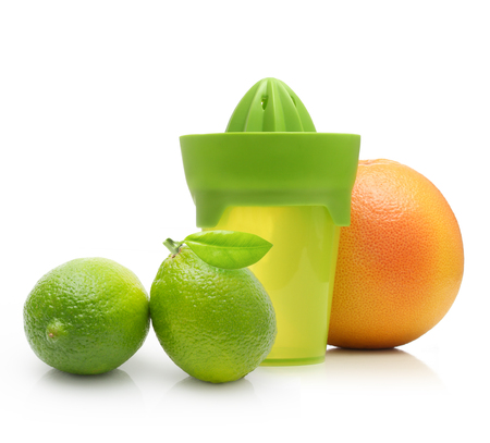 Green manual juicer and citrus fruit  isolated on white background. Stock Photo
