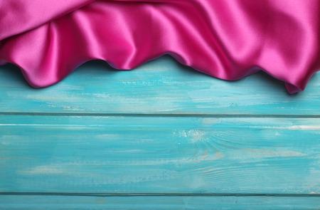 satin: Purple wavy silk on blue wooden background.