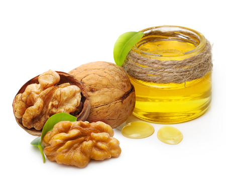 Walnut oil and nuts with leaf isolated on white background Foto de archivo