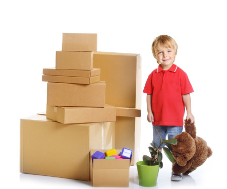 unpacking: Happy chid with unpacking cardboard boxes over white background. Stock Photo
