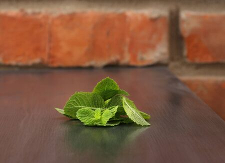 Green mint leaves on wooden table
