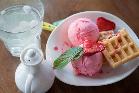 Belgium waffles with strawberries, mint and balls scoope ice cream on white plate Stock Photo