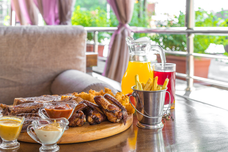 Grilled beef steak and Assorted delicious grilled meat with and cool drinks on the table of the summer veranda