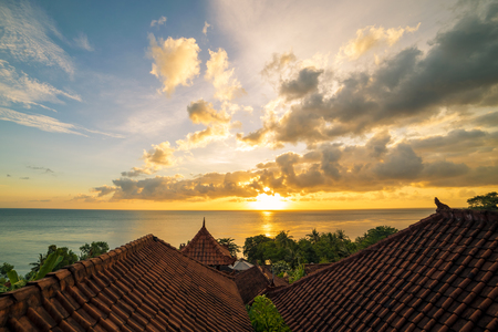 Traditional roofs of Balinese houses against the backdrop of the ocean and dawn in Amed, Bali, Indonesia