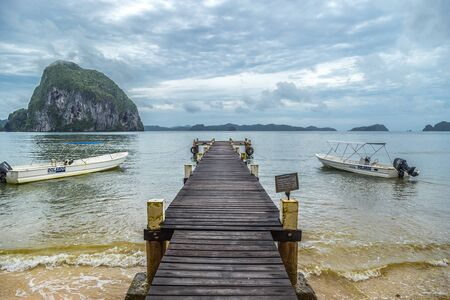 Pier with boats on the background of a tropical sea and rocky mountains in cloudy day, El Nido, Palawan, Philippines. August 2018. 版權商用圖片 - 137283323