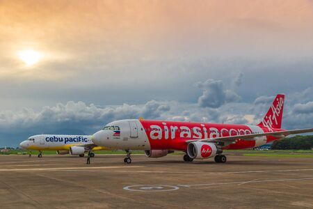 Low cost airlines Cebu Pacific and Air Asia aircraft at colorful sunset at Puerta Princesa Airport in Palawan island, Philippines. August 2018. 新聞圖片