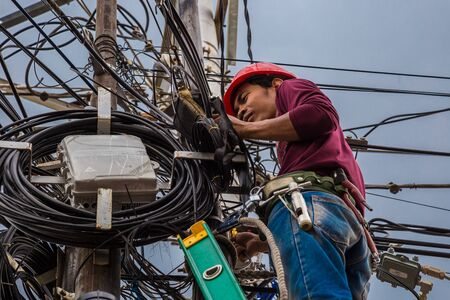 Indonesian electrician repair workers are to fix the line of network cable and wire on electric pole. Jakarta, Indonesia. Jule 2018 新聞圖片